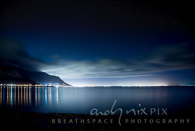 Night view of Muizenberg peak silhouetted by city glow, lights of Kalk Bay reflected in sea with stars and clouds in sky