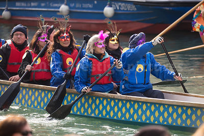 People paddling a boat wearing modern carnival masks