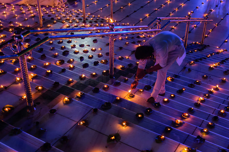 A Devotee at the Swami Narayan Temple Relights some of the Thousands of Butter Lamps that were Lit for Diwali