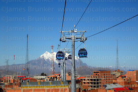 Blue Line cable car cabins above La Ceja, Mt Illimani in background, El Alto, Bolivia