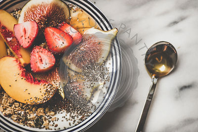 Healthy vegetarian breakfast bowl with yogurt, fruits and honey, close-up