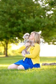 woman holding and kissing dog in grass