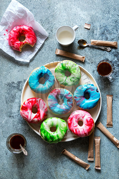 Donuts with marbled icing on a plate and coffee mugs on the table