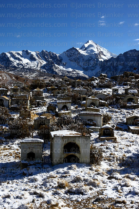 Milluni cemetery after fresh snowfall and Mt Huayna Potosi, Cordillera Real, Bolivia