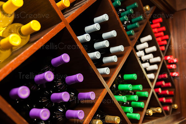 Stacks of wine bottles with colorful foils in a wine cellar