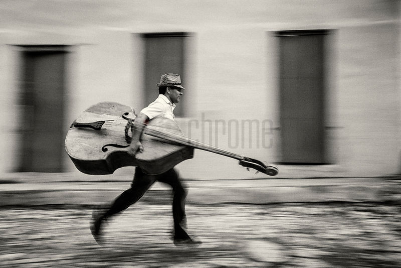 Musician Running to Work with Double Bass Under his Arm