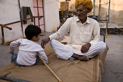 India - Rajasthan - A man and his grandchild on a charpoy above their house in Jaipur