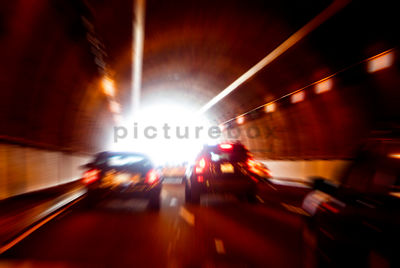 An atmospheric image of cars racing through a tunnel out into the daylight.