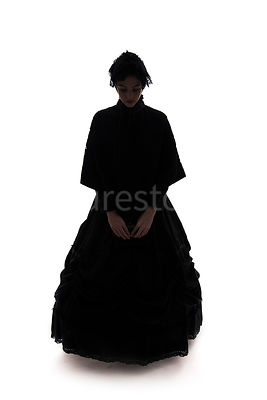 A Victorian woman, in a cape and hat, in silhouette – shot from eye level.