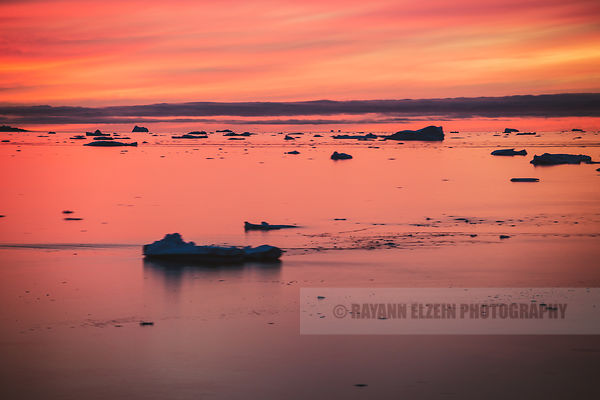 A long exposure of a very colourful sunset with the icebergs floating by in the Uummannaq fjord in Greenland