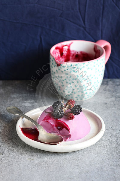 Blackberry panna cotta dessert on a plate decorated with fresh blackberry and a jug with blackberry sauce in background
