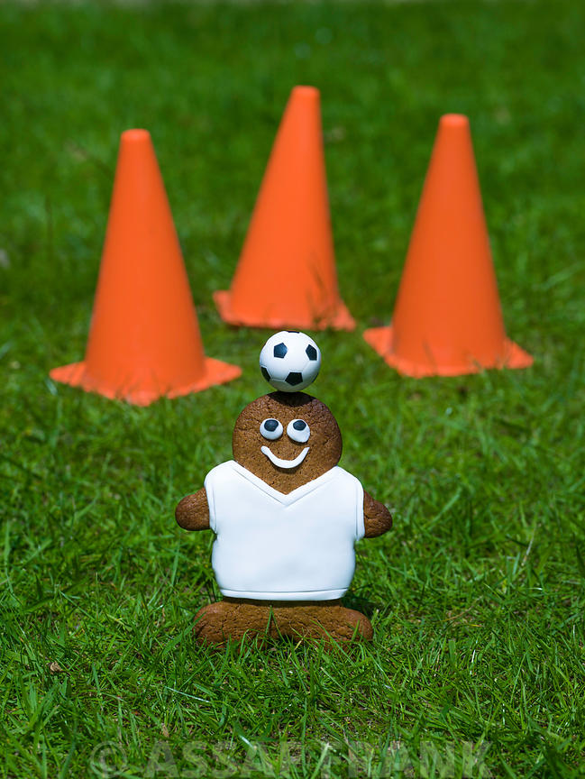 Gingerbread footballer with football and cone on grass