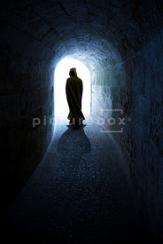 An atmospheric image of a mystery man, or woman, in a hooded cloak walking down a darkly lit underground tunnel / castle, loo...