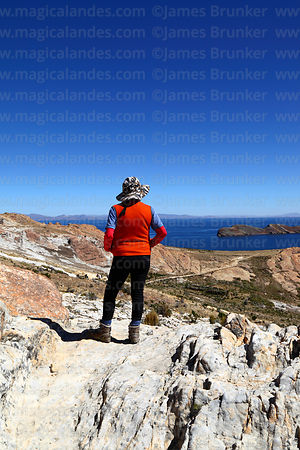 Tourist looking at view towards Sanctuary area and northern end of Sun Island, Lake Titicaca, Bolivia