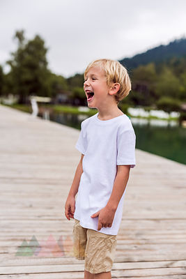 Laughing little boy standing on a jetty