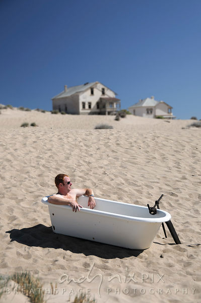 Man sitting in a Victorian bathtup outdoors on a sand dune in the desert, old abandoned and delapidated houses in the background