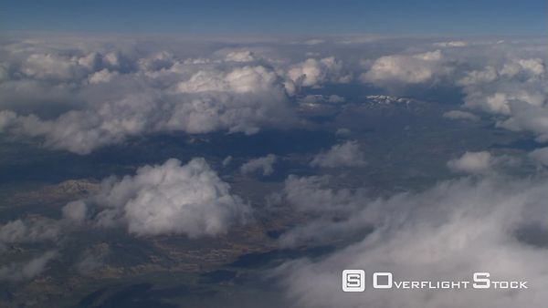 Flight alongside puffy clouds, passenger POV