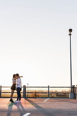 Young couple kissing on parking level at sunset