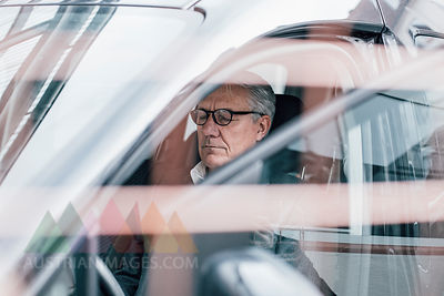 Senior businessman sitting in car with closed eyes