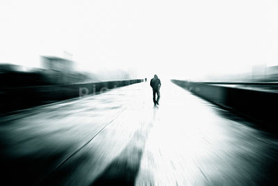 An atmospheric image of the silhouette of a mystery man walking over a bridge in the city.