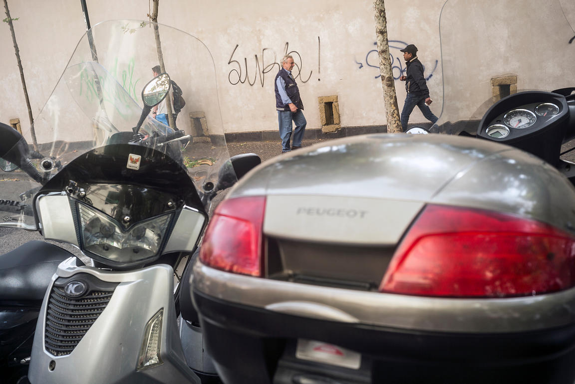 People walk past a wall covered in graffiti in the affluent Chiaia neighbourhood in Naples