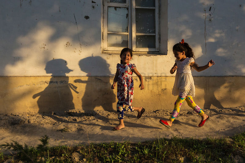 Children Running along a Dirt Trail at Sunset