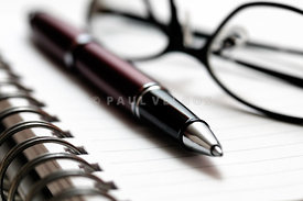Pen and Eyeglasses on Spiral Notebook
