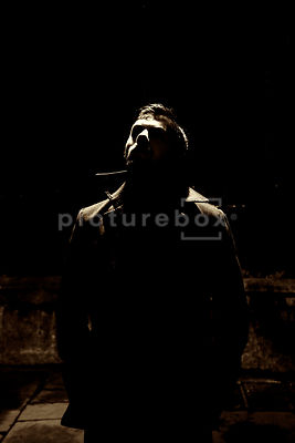 An atmospheric image of a mystery man lit by streetlight, in a dark alley, at night.