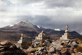 Stone cairns with crosses on hilltop, Guallatiri volcano in background, Las Vicuñas National Reserve, Region XV, Chile