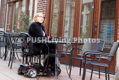 Woman using a mobilty scooter sitting at a sidewalk cafe