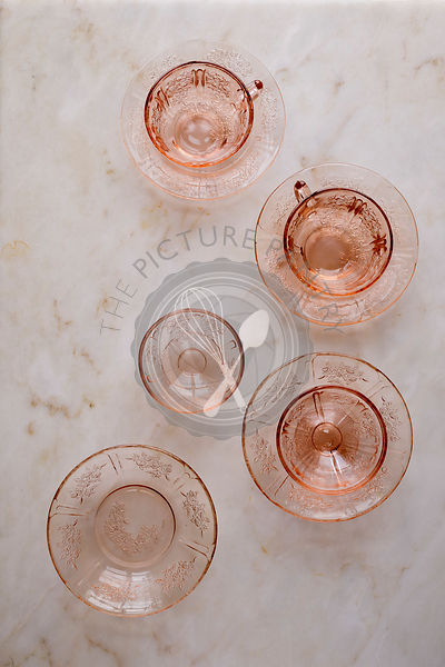 Empty pink cups and saucers on a marble background