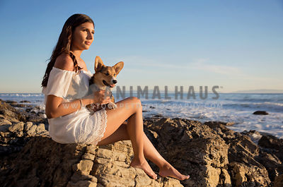 Hispanic young woman at a rocky beach with Pembrook Welsh Corgi puppy