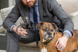 Brindle boxer dog standing next to man with beard wearing suit holding glass of red wine