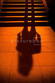 An atmospheric image of the long shadow of a mystery woman standing on some steps in Prague.