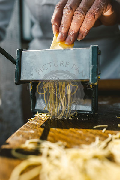 A WOMAN MAKING HOMEMADE PASTA IN THE TRADITIONAL WAY