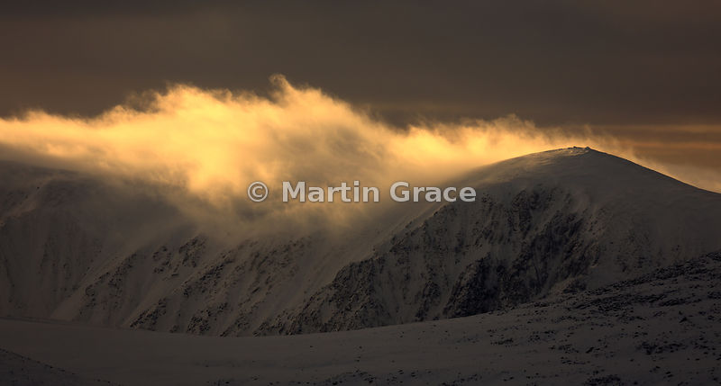 Late afternoon sun just catching cloud as it pours over the summit of Carn Eilrig, Cairngorm Mountains, Scotland