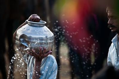 Collecting water in metal jugs from a communal water source, Pushkar, Rajasthan, India