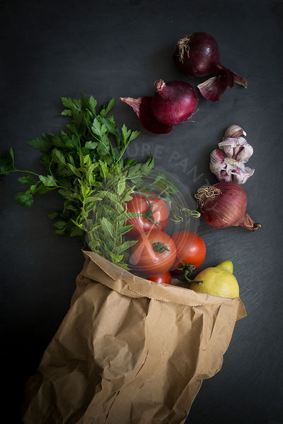 Vegetables in paper bag fresh from the market on slate background: Top view