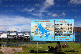 Signs in port with prices for visits to Uros Islands and information about Lake Titicaca, Puno, Peru