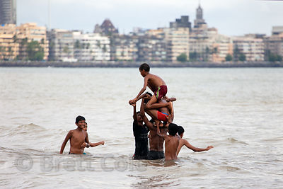 Swimmers play in the Arabian Sea at Chowpatty Beach, Mumbai, India.