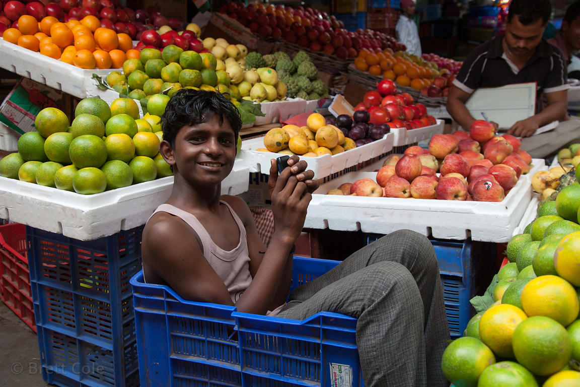 A worker sits in a crate at a fruit stall at Crawford Market, Mumbai, India.