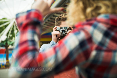 Teenage boy photographing his girlfriend, partial view