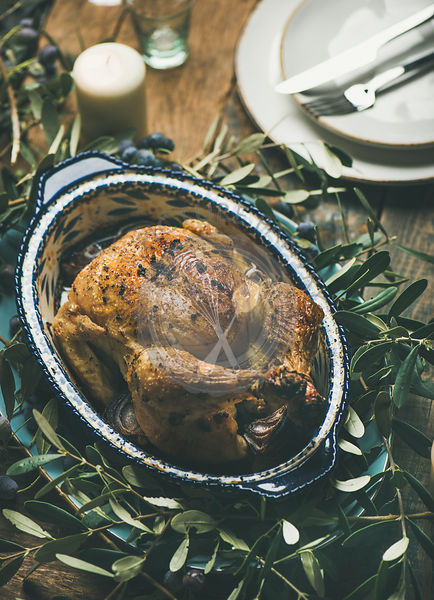 Whole roasted chicken for Christmas eve celebration decorated with olive tree branch