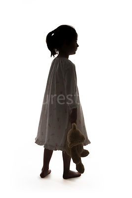 Silhouette of a little barefoot girl in a night dress, carrying a teddy – shot from mid level.
