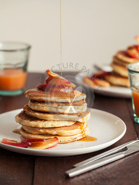 Stack of American pancakes with caramalised apple and maple syrup