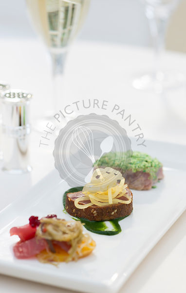 Trio of Tuna served with white wine in a restaurant setting.