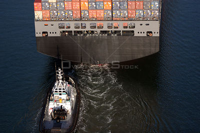 Looking down upon a tug steaming behind a cargo ship loaded with crates, San Francisco Bay, California.