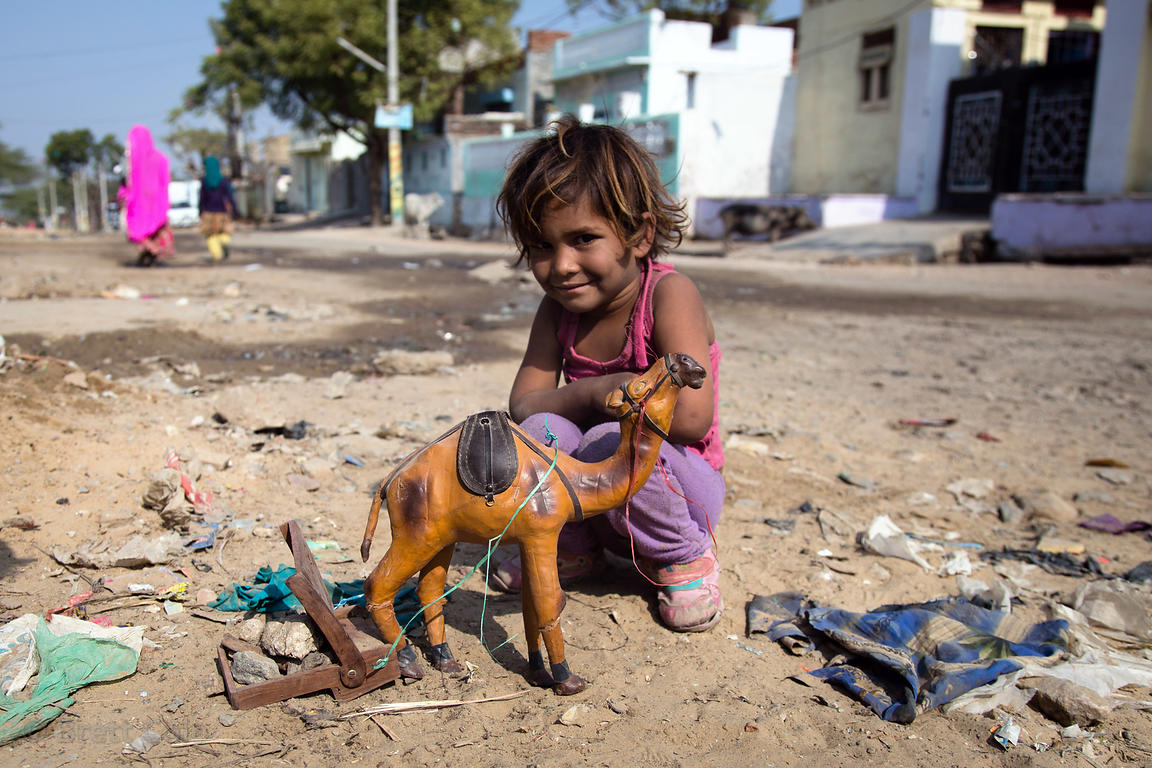 A girl plays with a toy camel, Pushkar, Rajasthan, India. A favorite photo, this was completely unstaged, she even chose to s...