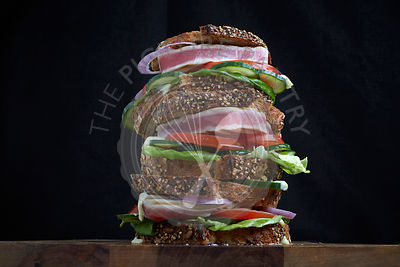Fresh Tuna Steak Sandwich stacked with lettuce, tomato and cucumber on sliced astisan bread.