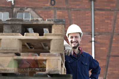 Smiling worker behind pallets